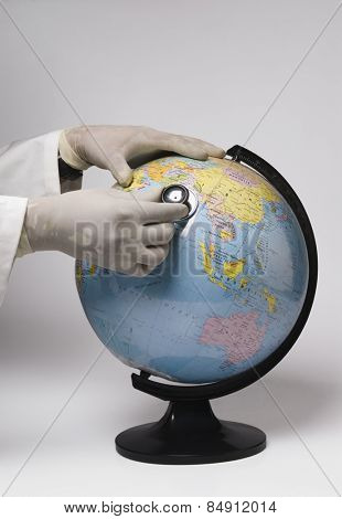 Close-up of a doctor's hands examining a globe with a stethoscope