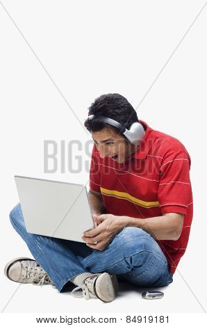 Man listening to headphones while using a laptop
