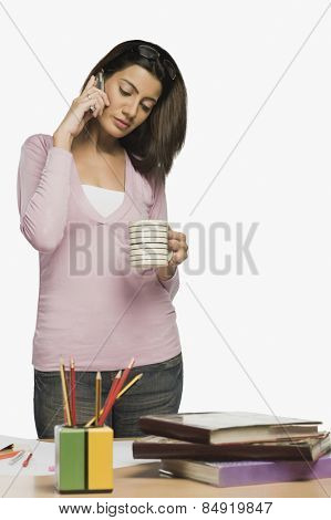 Female fashion designer drinking coffee and talking on a mobile phone