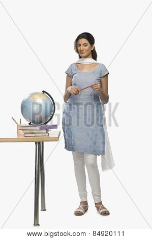 Female teacher holding a pen near a desk