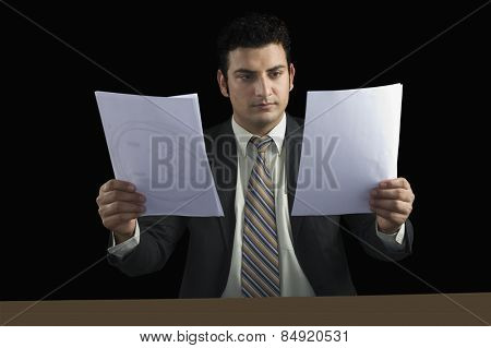 Businessman holding two documents