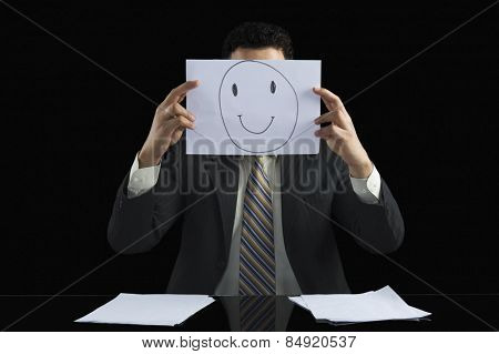 Businessman holding a smiley face paper in front of his face
