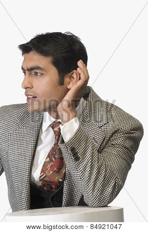 Businessman cupping his ears