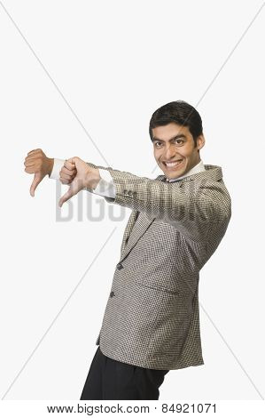 Businessman showing thumbs down and smiling