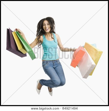 Woman carrying shopping bags and jumping on a trampoline