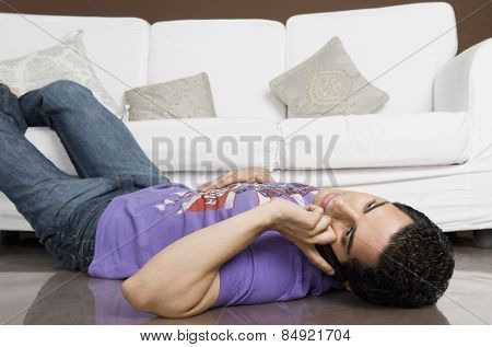 Man lying on the floor and talking on a mobile phone