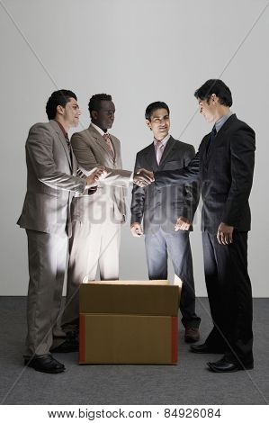 Two businessmen shaking hands over an illuminated cardboard box with their colleagues standing beside them