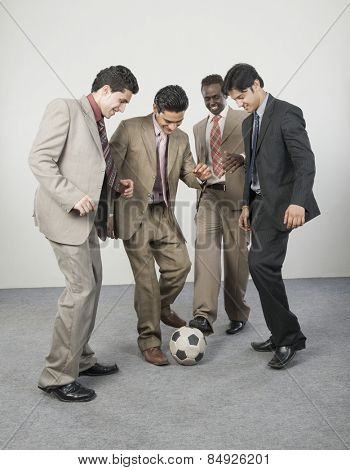Four businessmen playing with a soccer ball