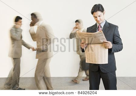 Businessman reading a newspaper with his colleagues in the background
