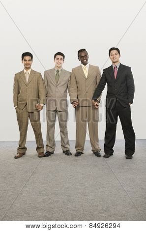 Portrait of four businessmen standing together with holding hands