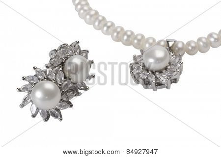 Close-up of pearl earrings with a pearl necklace