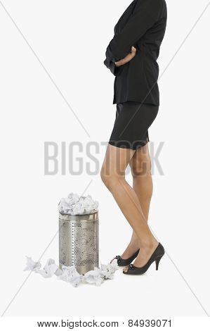 Businesswoman standing in front of a wastepaper basket