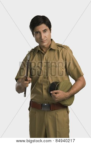 Portrait of a police officer holding a nightstick and a cap