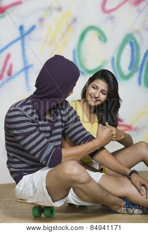 Couple sitting with a skateboard in front of a graffiti covered wall