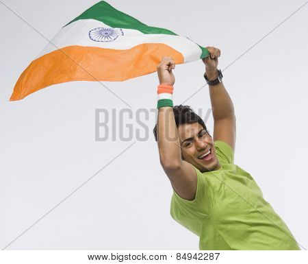 Portrait of a man holding aloft an Indian flag