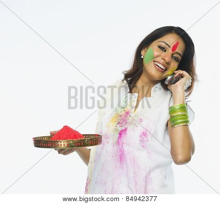 Woman holding Holi colors and talking on a mobile phone