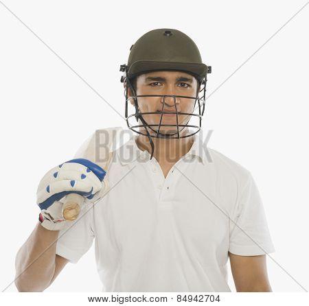 Portrait of a cricket batsman holding a bat and smiling