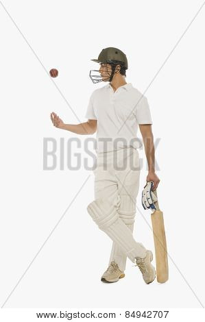 Cricket batsman tossing a cricket ball