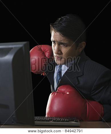 Businessman punching a desktop pc