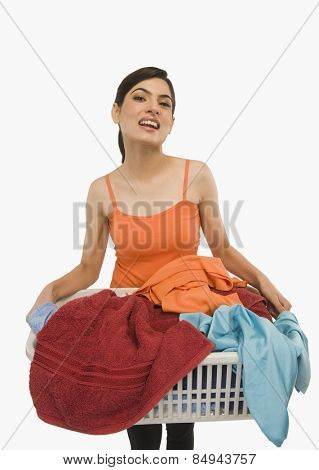Woman holding laundry basket filled with clothing