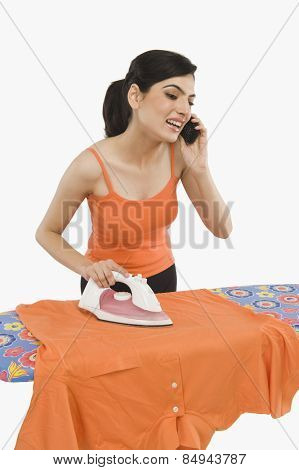 Woman ironing and talking on a mobile phone