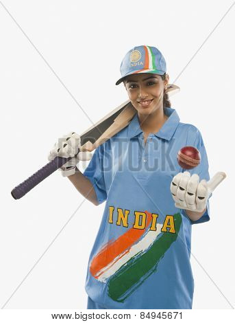 Portrait of a female cricketer tossing a cricket ball and smiling