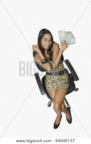 Woman holding currency notes and looking excited