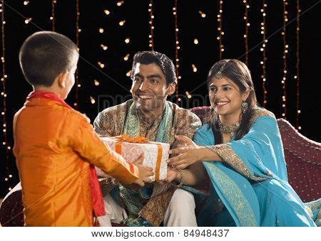 Couple giving Diwali gift to their son