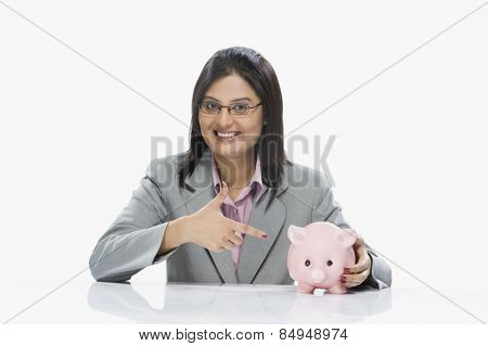 Businesswoman pointing at a piggy bank
