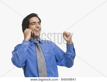 Businessman raising fist while talking on mobile phone