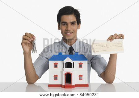 Real estate agent showing keys and a check near a model home