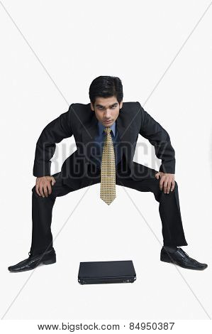 Businessman crouching in front of a laptop