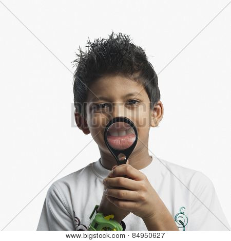 Portrait of boy holding magnifying glass and smiling