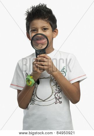 Portrait of a boy holding a magnifying glass and smiling