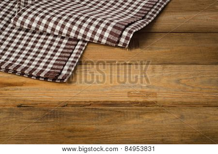 Brown Checkered Tablecloth Textile On A Wooden Background