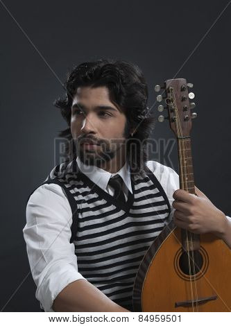 Musician holding a lute and thinking