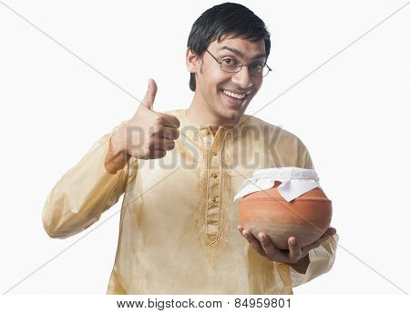Bengali man holding a pot of rasgulla and showing thumbs up sign
