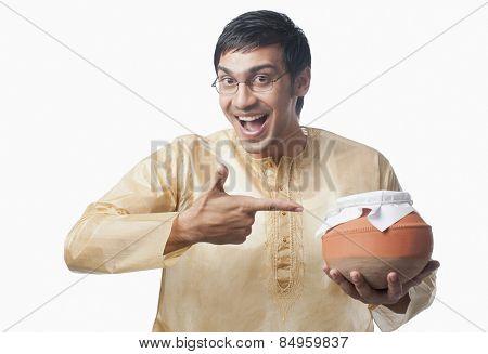 Bengali man pointing towards a pot of rasgulla