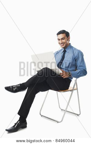Bengali businessman using a laptop on a chair