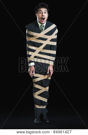Businessman tied up with adhesive tape looking shocked