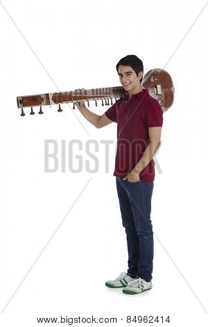Man carrying a sitar on his shoulders and smiling