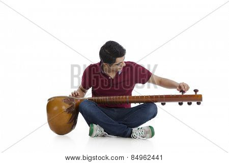 Man sitting on the floor and adjusting his sitar