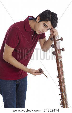 Man leaning over his broken sitar
