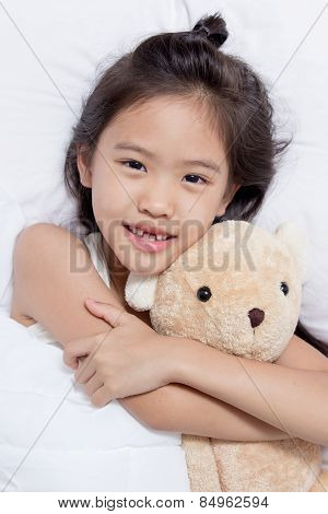 Adorable little Asian girl sleep on her bed with bear doll