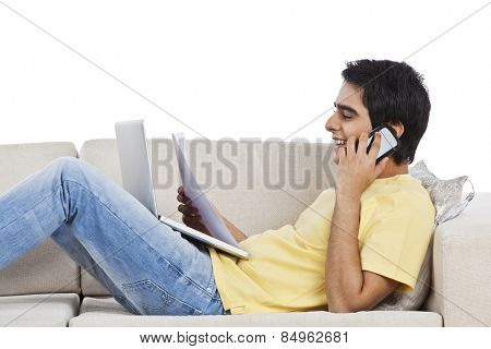 Man lying on a couch and talking on a mobile phone with holding a paper