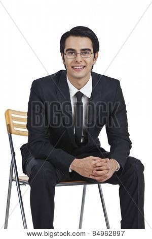 Portrait of a businessman sitting on a chair with his hands clasped
