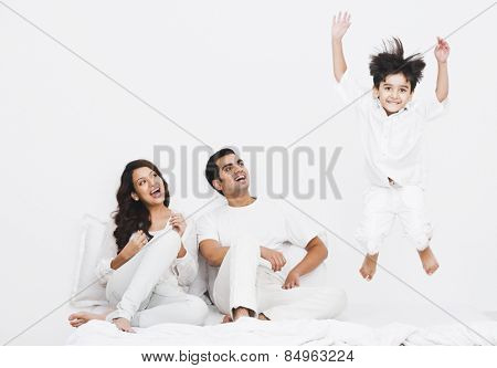 Happy boy jumping on the bed with his parents