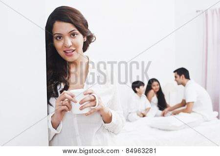 Woman enjoying a cup of coffee with her family in the background