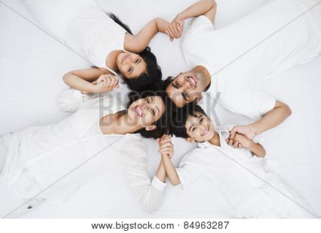 High angle view of a happy family lying on the bed