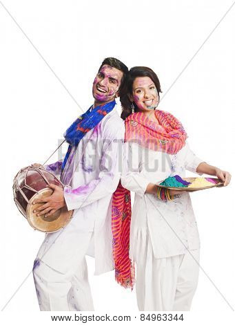 Couple celebrating Holi with colorful paints and a drum
